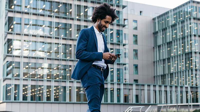 man looking down at phone in front of glass building