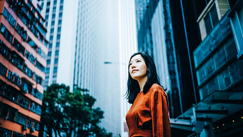 woman looking off in front of skyscrapers